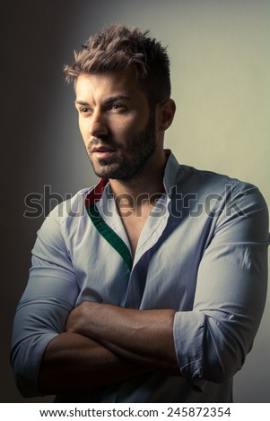 Vintage portrait of a smart serious young man standing against studio background  - stock photo