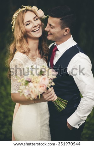Vintage portrait of a young hipster couple posing in wedding suite and dress at sunset in the forest - stock photo