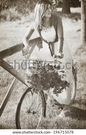 Vintage portrait of a young woman on a bike with flowers