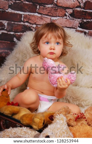 vintage portrait of adorable baby girl  sitting in old suitcase and playing mascots - stock photo