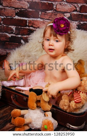vintage portrait of adorable baby girl with purple flower on hair band sitting in old suitcase and playing mascots - stock photo