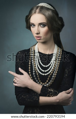 vintage portrait of beautiful brunette woman posing like a antique dame with precious crown and necklaces, retro hair-style  - stock photo