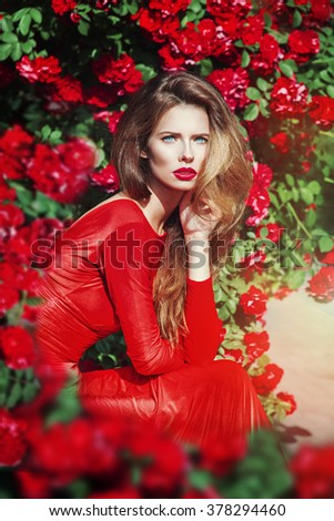 Vintage portrait of beautiful gorgeous woman in red dress in the garden full on roses. Film effect - stock photo