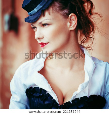 Vintage portrait of beautiful woman in black corset with decollete. Victorian style. Instagram warm colors effect. - stock photo