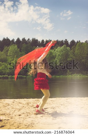 Vintage portrait of cute girl dancing with red Scarf at the river - stock photo