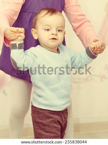vintage portrait of cute little boy walking on a floor, children help - stock photo