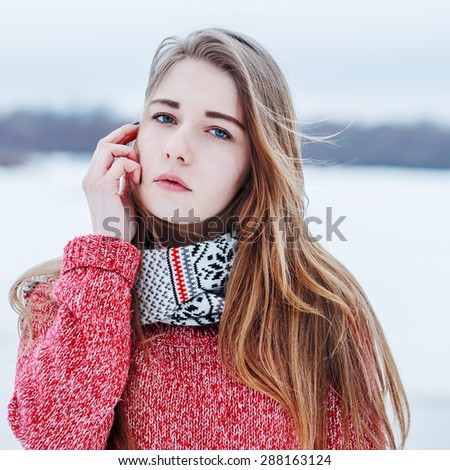 vintage portrait of cute young pretty attractive girl with long blond hair red warm sweater and white scarf on natural background in field. Outdoor winter photo in soft light - stock photo