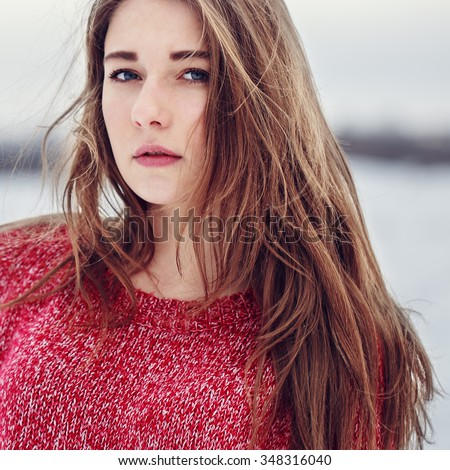 vintage portrait of cute young pretty attractive girl with long blonde hair red warm sweater  on natural background in field. Outdoor winter photo in soft light - stock photo