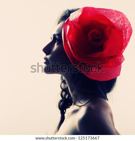 Vintage portrait of fashion glamour girl with red flower in her hair, over white. Studio shot.