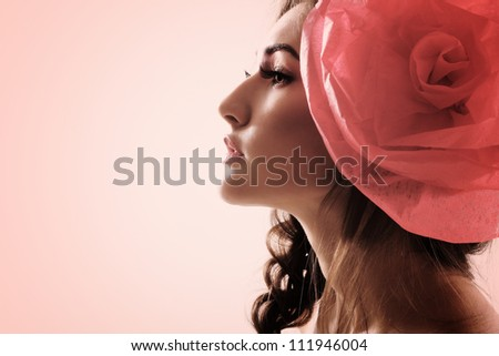 Vintage portrait of fashion glamour girl with red flower in her hair. Studio shot, toned. - stock photo