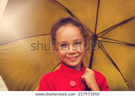 vintage portrait of happy school girl in a red jacket holding an yellow umbrella in autumn day - stock photo