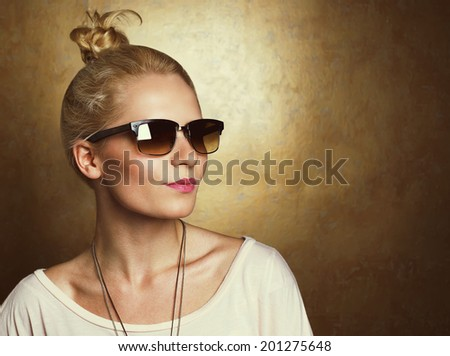 Vintage portrait of young beautiful blonde hipster girl in vintage glasses over golden background. Copy space. Studio shot