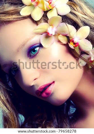 Vintage portrait of young beauty with orchid flowers