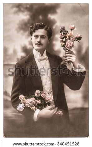 Vintage portrait of young man with rose flowers. Typical for this period mans look. Retro picture with original film grain and blur - stock photo