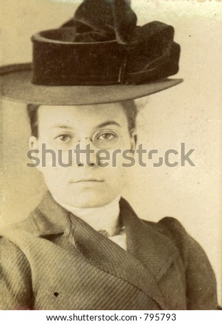 Vintage print of a young woman in a stylish hat. Circa 1910 print has scratches, artifacts, fading and solarization qualities. - stock photo