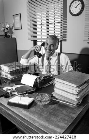 Vintage professional journalist on the phone working at office desk. - stock photo