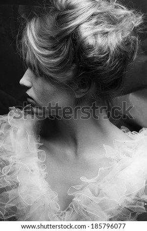 Vintage profile portrait of a crazy queen like girl posing over wrinkled black paper background. Retro style. Black and white (monochrome) studio shot