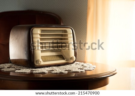 Vintage radio on round table with doily and living room on background. - stock photo