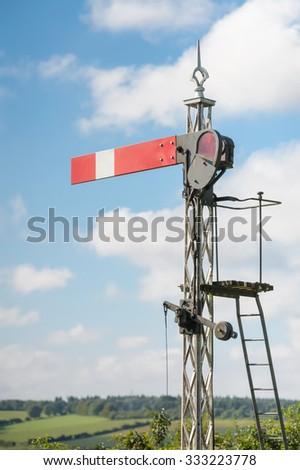 vintage railroad semaphore signal against blue sky - stock photo