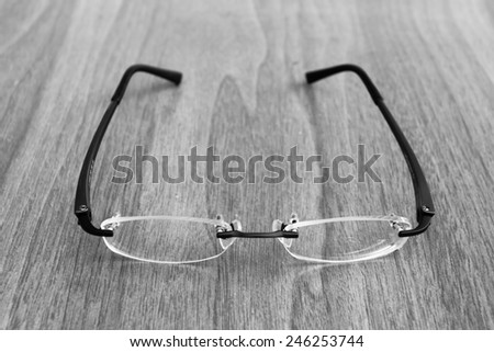 vintage Reading glasses on the wood table - stock photo