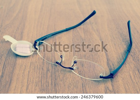 vintage Reading glasses on the wood table with medicine - stock photo