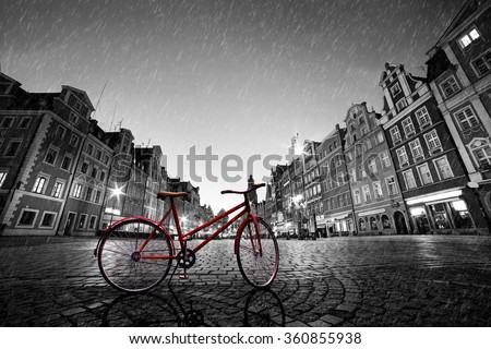 Vintage red bike on cobblestone historic old town in rain. Color in black and white. The market square at night. Wroclaw, Poland. - stock photo