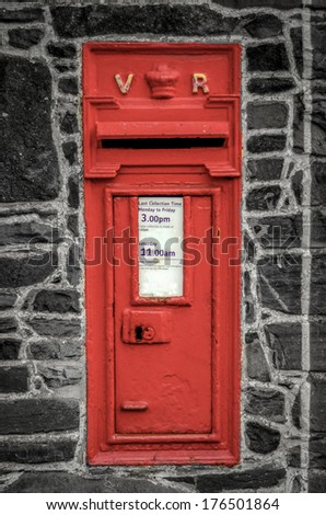 Vintage Red British Post Box In Black And White Stone Wall - stock photo