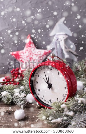 Vintage red clock, decorative star, branches fur tree and red berries on aged  wooden background. Selective focus. Drawn snow effect.