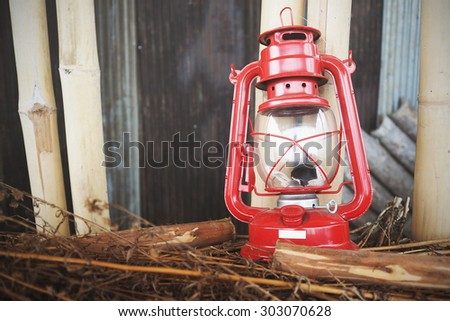 Vintage red oil lamp on dried grass. Vintage Interiors. Toned image. - stock photo