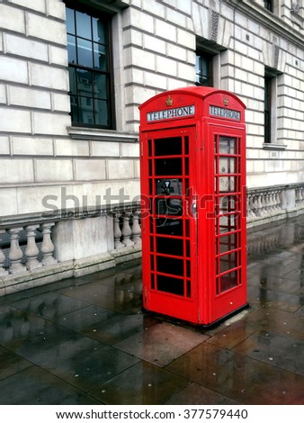 Vintage red phone cabin in London,  monumental item on a rainy day - stock photo
