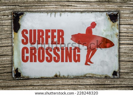 Vintage Red Retro Surfer Crossing Warning Sign On Wooden Background In Hawaii - stock photo