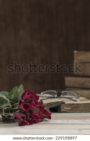 Vintage Red rose and old book on wooden table