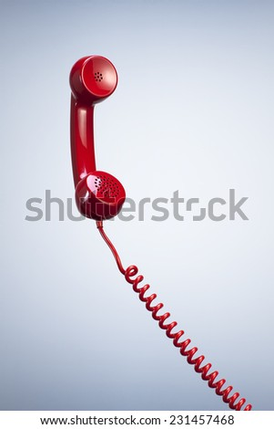 Vintage Red Telephone Receiver with Hanging Cable isolated Beautiful Studio Background. Top View with Copy Space for Text - stock photo