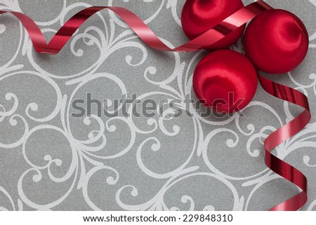 Vintage red wrapped ornaments and red ribbon on a silver scroll background - stock photo