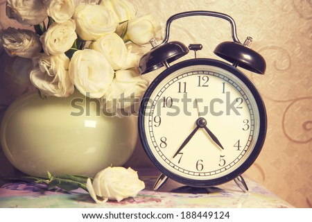 vintage retro clock  and ikebana on table - stock photo