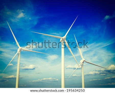 Vintage retro effect filtered hipster style image of green renewable energy concept - wind generator turbines in sky