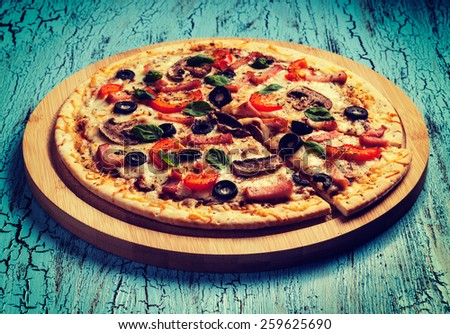 Vintage retro effect filtered hipster style image of ham pizza with capsicum, mushrooms, olives and basil leaves on wooden board on blue table - stock photo