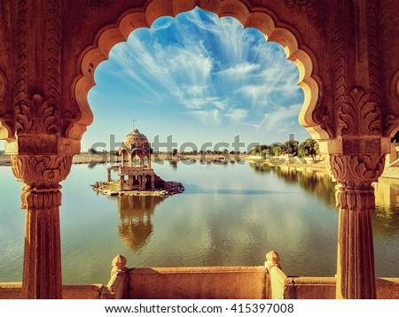 Vintage retro effect filtered hipster style image of Indian landmark Gadi Sagar - artificial lake view through arch. Jaisalmer, Rajasthan, India - stock photo