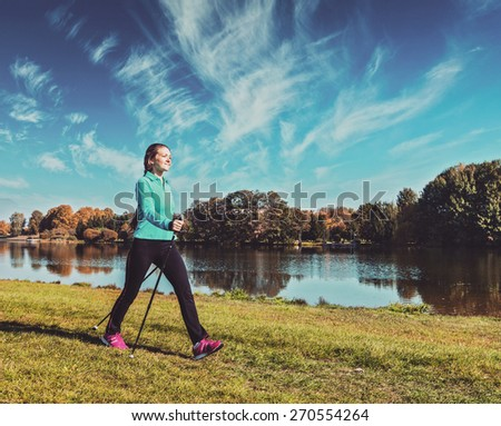 Vintage retro effect filtered hipster style image of nordic walking adventure and exercising - young woman hiking with nordic walking poles in park along river - stock photo