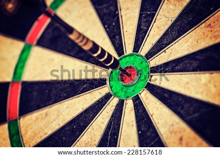 Vintage retro effect filtered hipster style image of   -Success hitting target aim goal achievement concept background - dart in bull's eye close up - stock photo