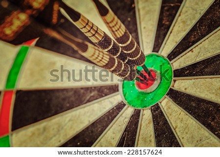Vintage retro effect filtered hipster style image of - Success hitting target aim goal achievement concept background - three darts in bull's eye close up - stock photo