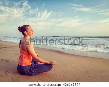 Vintage retro effect hipster style image of woman doing yoga - meditating and relaxing in Padmasana Lotus Pose) with chin mudra outdoors at tropical beach on sunset - stock photo