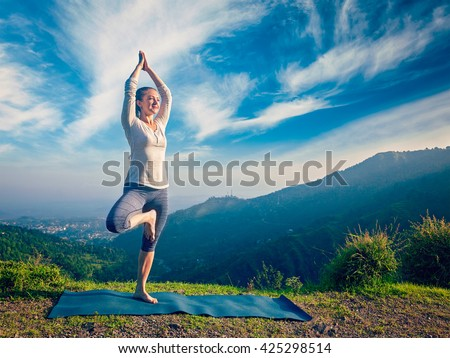 Vintage retro effect hipster style image of woman practices balance yoga asana Vrikshasana tree pose in Himalayas mountains outdoors in the morning. Himachal Pradesh, India. Panorama