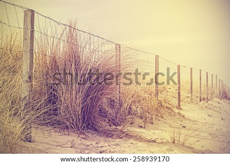 Vintage retro filtered photo of fence on dune, nature background.