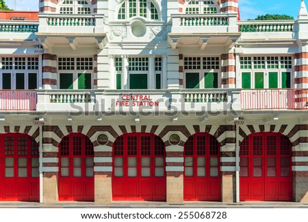 Vintage retro fire station building facade with red gates and brick walls - stock photo