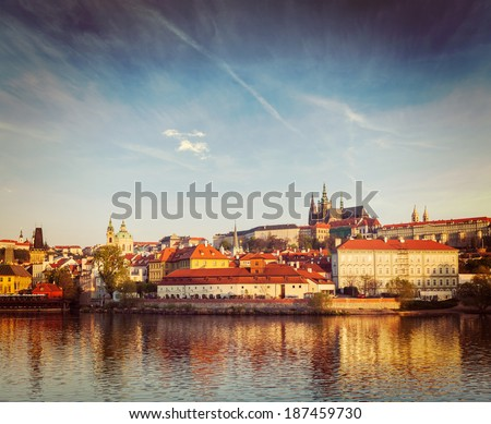 Vintage retro hipster style travel image of Gradchany (Prague Castle) and St. Vitus Cathedral over Vltava river on sunset - stock photo