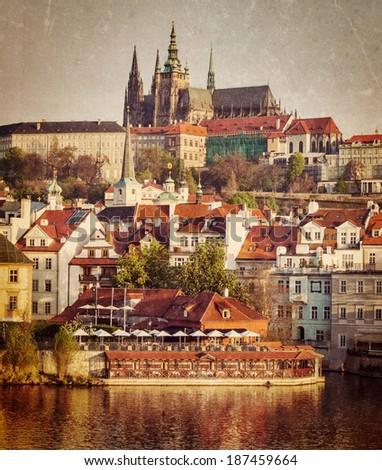 Vintage retro hipster style travel image of Mala Strana and  Prague castle over Vltava river with grunge texture overlaid. Prague, Czech Republic - stock photo