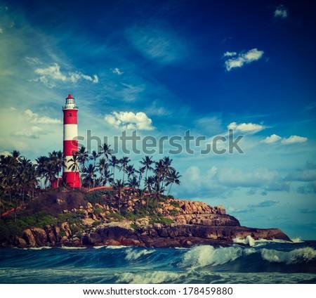 Vintage retro hipster style travel image of old lighthouse and waves of  sea. Kovalam (Vizhinjam) Kerala, India - stock photo