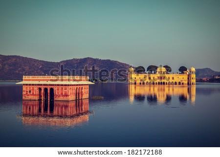 Vintage retro hipster style travel image of Rajasthan landmark - Jal Mahal (Water Palace) on Man Sagar Lake on sunset.  Jaipur, Rajasthan, India - stock photo