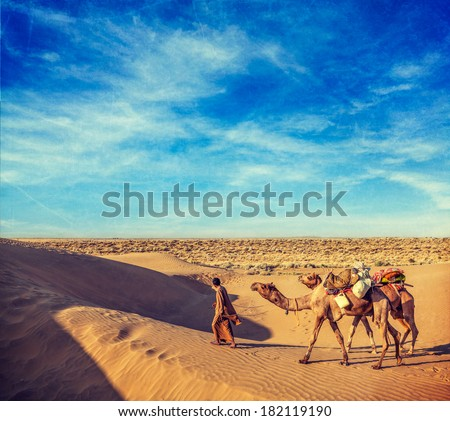 Vintage retro hipster style travel image of Rajasthan travel background - India cameleer (camel driver) with camels in dunes of Thar desert with grunge texture overlaid. Jaisalmer, Rajasthan, India - stock photo